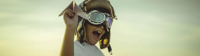 """Edmond Halley pensioenadvies foto met een jongetje dat speelt dat hij een piloot is. De foto symboliseert dat """"later""""ook nu al aanwezig is. In onze adviezen brengen we deze ook bij elkaar."""